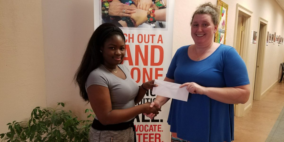 Student receiving scholarship from woman at United Way