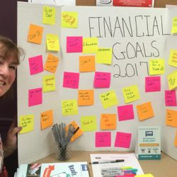 Woman beside poster with financial goals on sticky notes